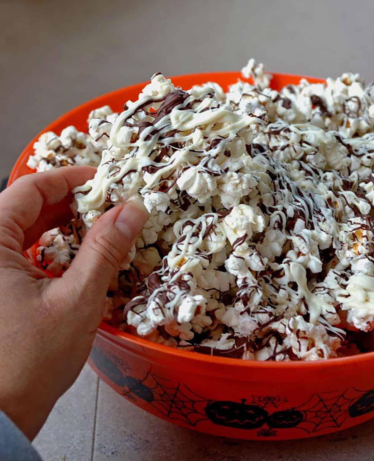 hand grabbing chocolate-covered popcorn from orange Halloween bowl