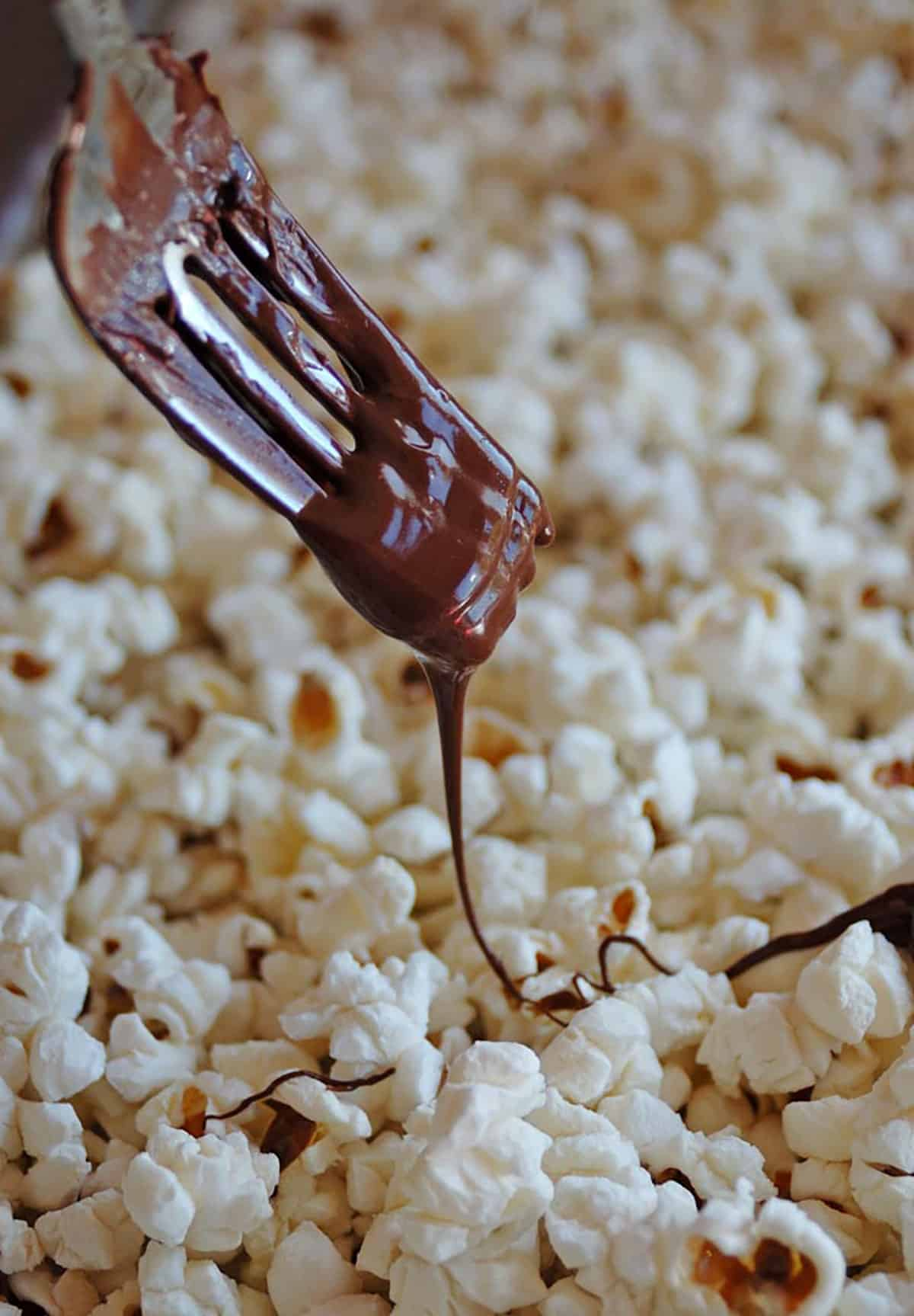 fork drizzling chocolate on popcorn
