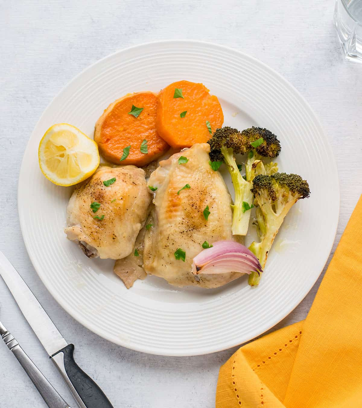 plate of roasted chicken thighs with broccoli, sweet potatoes, lemon, red onion