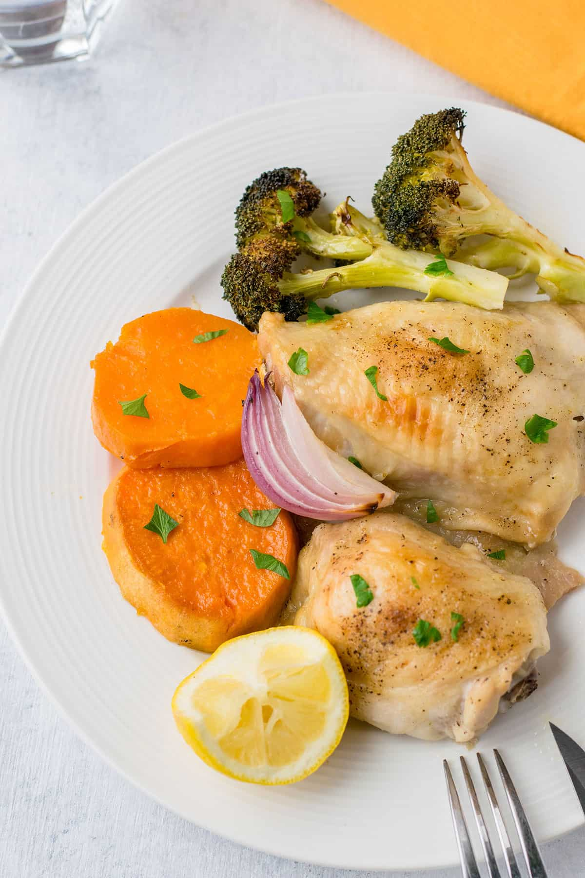 closeup of roasted chicken thighs, sweet potatoes, broccoli, red onion, lemon on plate