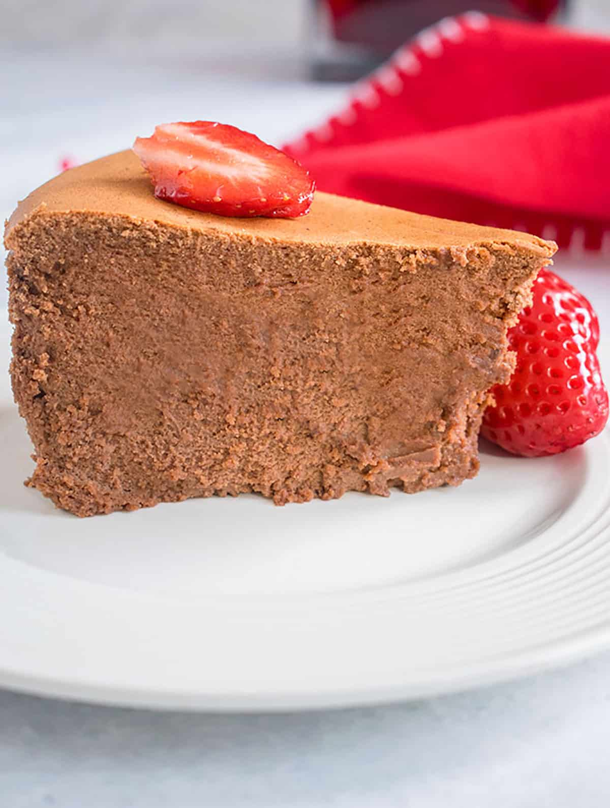 tall slice of chocolate cheesecake with strawberries