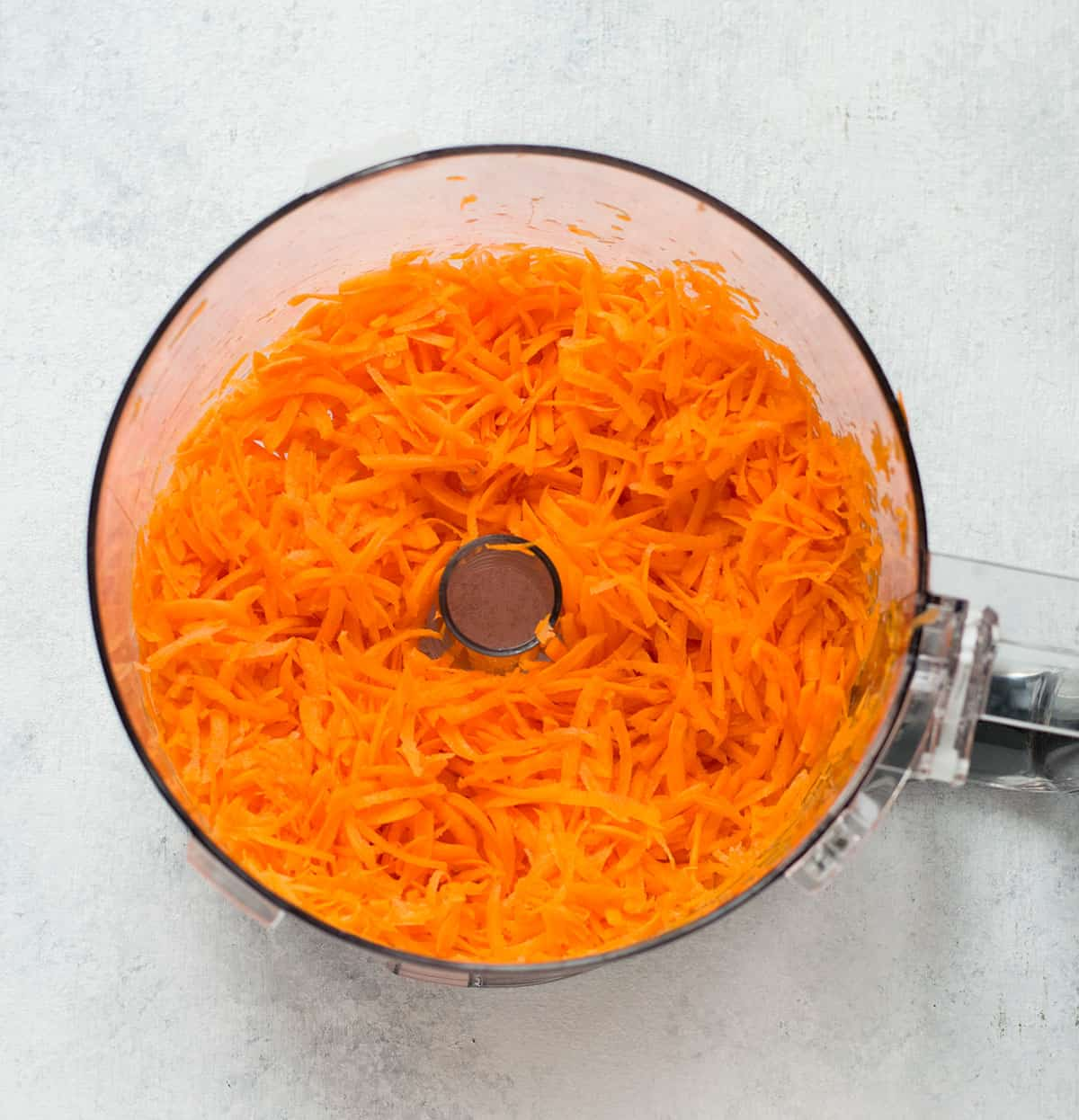 shredded carrots in bowl of food processor