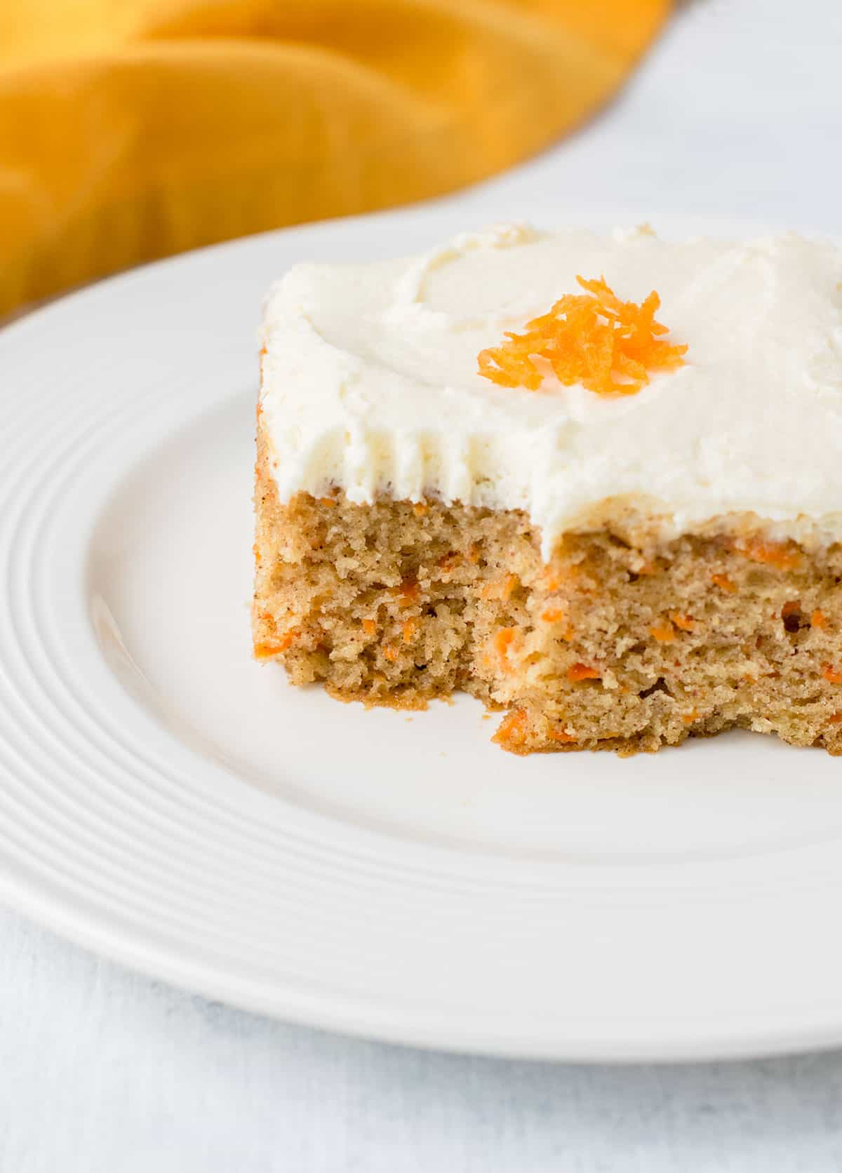 slice of single-layer carrot cake with bite missing