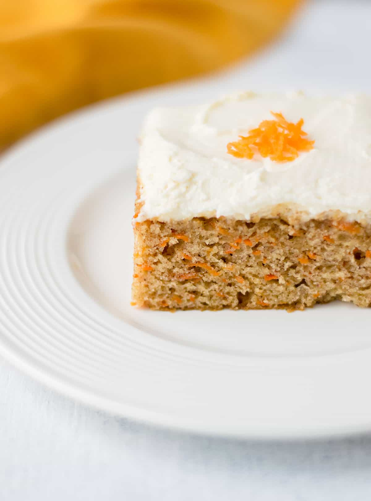 slice of square carrot cake on white plate